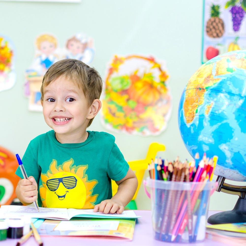Bambino sorridente che scrive un un quaderno